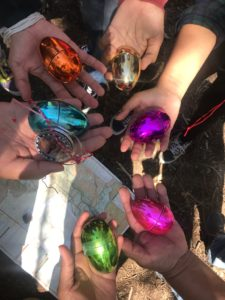Six people's hands, each of which holding a differently colored metallic egg.